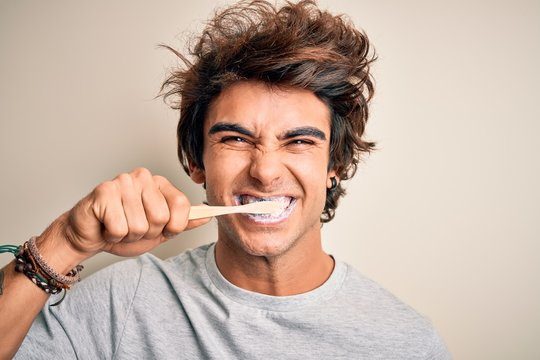 Young handsome man smiling happy. Standing with smile on face whasing tooth using toothbrush over isolated white background
