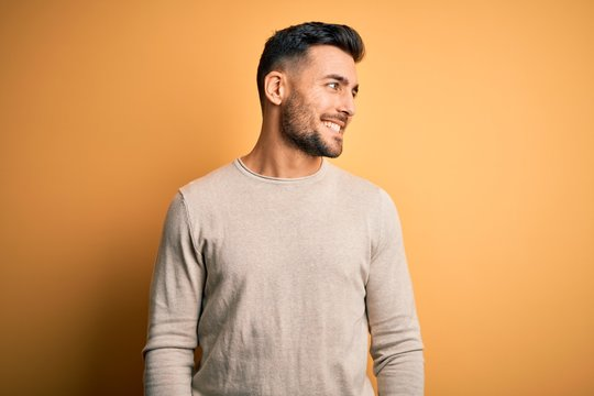 Young handsome man wearing casual sweater standing over isolated yellow background looking away to side with smile on face, natural expression. Laughing confident.