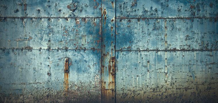 スタッドのある古びた青い門扉のテクスチャー