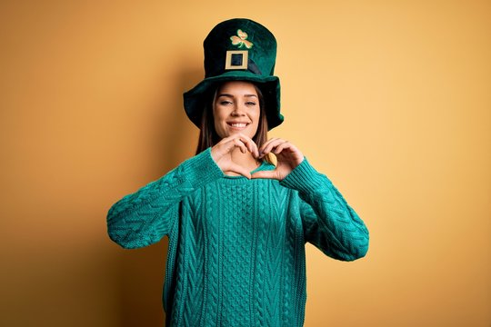 Young beautiful brunette woman wearing green hat with clover celebrating saint patricks day smiling in love doing heart symbol shape with hands. Romantic concept.