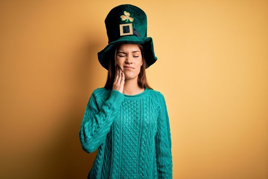 Young beautiful brunette woman wearing green hat with clover celebrating saint patricks day touching mouth with hand with painful expression because of toothache or dental illness on teeth. Dentist