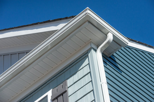 Colonial white gutter guard system, fascia, drip edge, soffit providing ventilation to the attic, with pacific blue vinyl horizontal siding at a luxury American single family home neighborhood USA