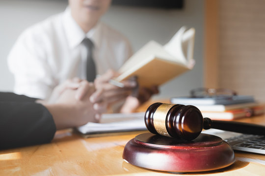 Business woman and lawyers discussing by lawyer book with brass scale on wooden desk in office. Law, legal services, advice, Justice concept.