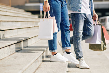 Cropped image of couple walking down the stairs of mall after shopping together Wall mural