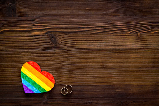 LGBT weddings. Rainbow heart near rings on wooden background top-down copy space