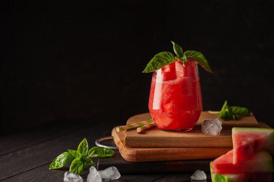 Refreshing cold summer drink watermelon slushie with basil on dark wooden background
