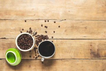 Wall Murals Cafe cup with fresh coffee and a can with coffee grains, coffee beans are scattered on a wooden table. Banner. Coffee concept, plantation, processing, collection. Top view, flat lay