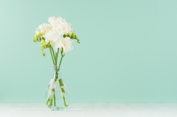 Fresh white freesia flowers in elegant transparent vase on soft light green mint menthe wall and white wood table, copy space.