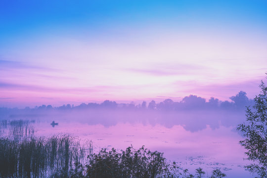 Magic sunrise over the lake. Misty early morning, rural landscape, wilderness, mystical feeling. Serenity lake in magical light