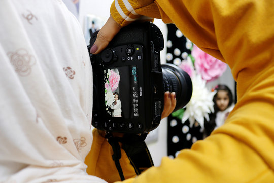 Jassem, 24, an Iraqi nurse takes picture of girl during her other photography job in Baghdad