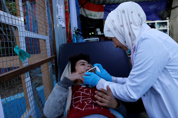 Jassem, 24, an Iraqi nurse provides pain relief to a boy in Baghdad