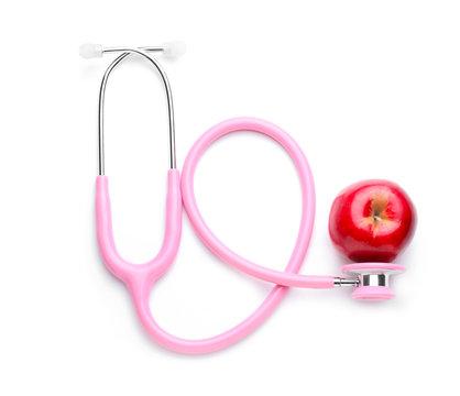 Fresh apple and stethoscope on white background