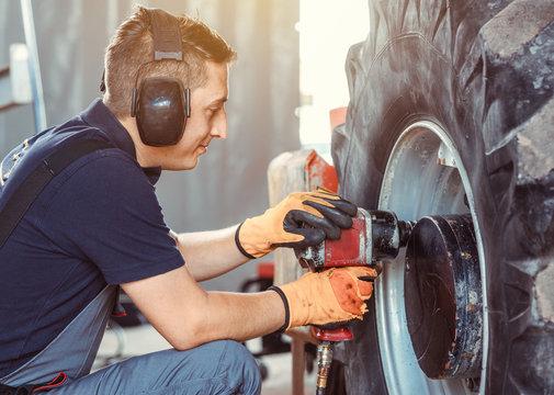 farm machine mechanic working on wheel