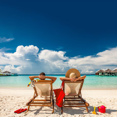 Fototapete - Couple in loungers on beach at Maldives