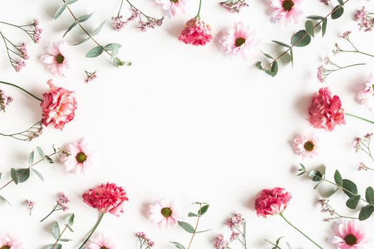 Flowers composition. Frame made of pink flowers and eucalyptus branches on white background. Valentines day, mothers day, womens day concept. Flat lay, top view