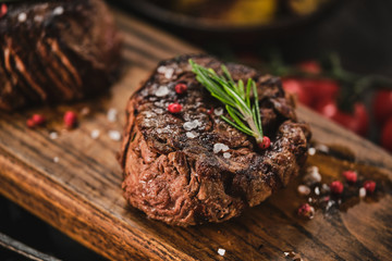 Foto op Aluminium Steakhouse Grilled fillet steaks on wooden cutting board. Succulent thick juicy portions of grilled fillet steak served with tomatoes and roast potatoes on an old wooden board.