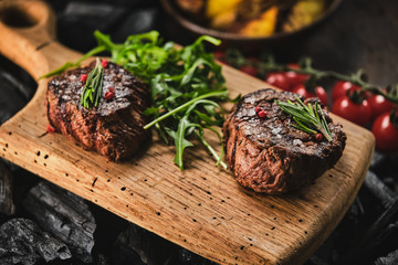 Foto auf AluDibond Steakhouse Grilled fillet steaks on wooden cutting board. Succulent thick juicy portions of grilled fillet steak served with tomatoes and roast potatoes on an old wooden board.