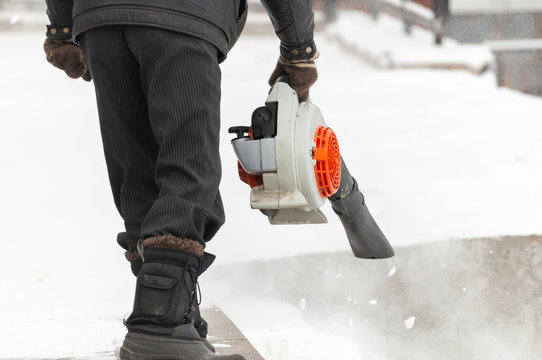 Man cleans street from snow with blower