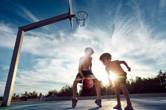 Zwei coole jungs spielen Basketball beim Sonnenuntergang am Meer.