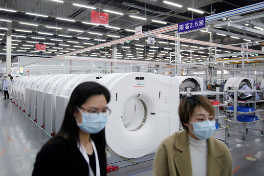 Employees wearing face masks are seen at a workshop of computed tomography (CT) scanners of medical device firm Siemens Healthineers in Shanghai