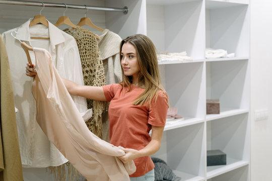 Young adult girl standing near wardrobe,  choosing wear