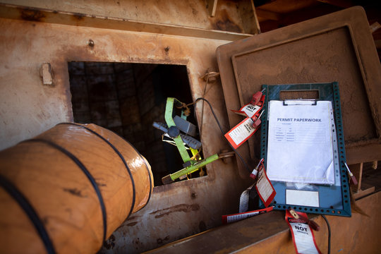Wide angle pic of permit to work paper clipping on isolation control permit board together with red personal danger locks and tags at confined space entry exit door ventilation fan