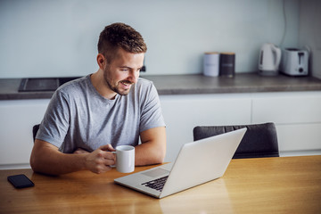 Young smiling man dressed casual sitting at dining table, holding mug with morning coffee and looking at laptop. He is visiting sites for online dating.