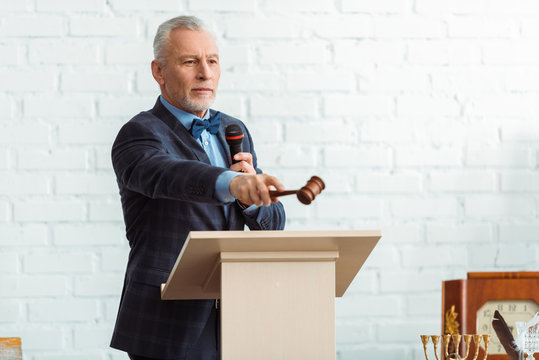 handsome auctioneer in suit holding microphone and pointing with gavel during auction