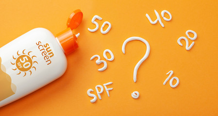 Sunscreen on orange background. Plastic bottle of sun protection and white cream in the form of question mark and numbers SPF. How to choose a sunscreen