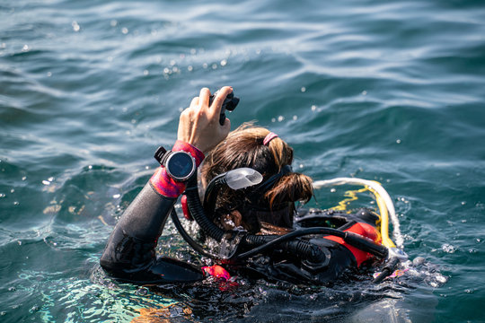 An Asian scuba diving girl with back wet suit waring dive computer at wrist