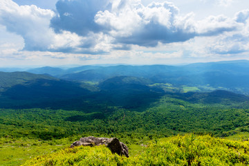 view in to the valley from the top of a mountain. huge rocks on the grassy hillside. clouds on the sky. beautiful sunny weather with dappled light. freedom in tourism concept