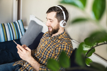 Man listens to music in headphones on the sofa at home, looking at mobile phone screen