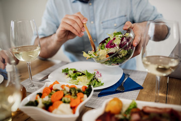 Keuken foto achterwand Koken Close-up of man pouring salad while having lunch at dining table.