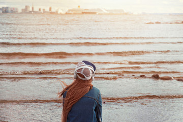 Tuinposter girl in blue jeans jacket and red hair sits back on the beach in cap and headphones on sea coast and looks into the distance at cruise liners