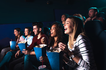 Group of cheerful people laughing while watching movie in cinema. Wall mural