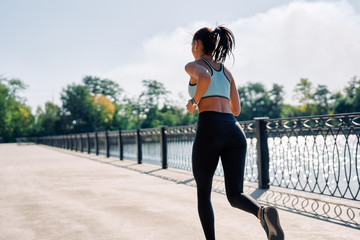 Back view of fit woman running outdoors by river