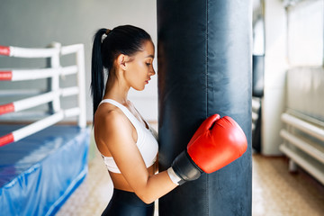 Sporty young woman wearing boxing gloves posing in gym