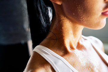 Close up shoulders and neck of sporty girl in drop of sweat on skin after workout