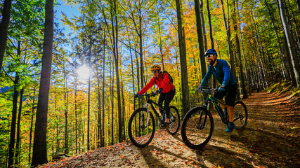 Wall Mural - Cycling woman and men riding on bikes at sunset mountains forest landscape. Couple cycling MTB enduro flow trail track. Outdoor sport activity.