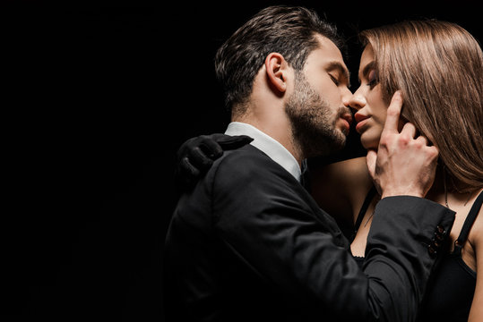 side view of handsome man in suit kissing attractive woman isolated on black