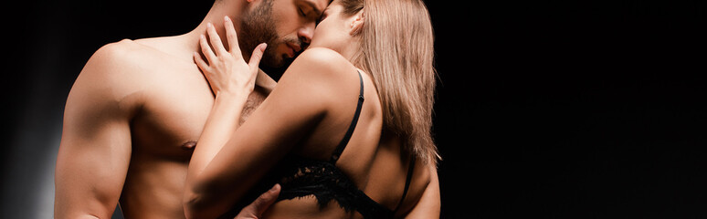 panoramic shot of shirtless man with closed eyes kissing woman on black
