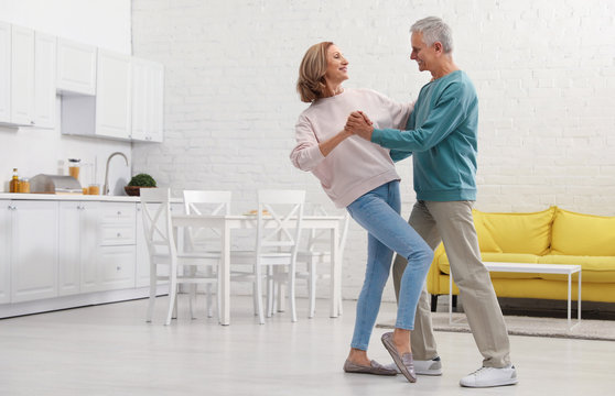 Happy senior couple dancing together in kitchen