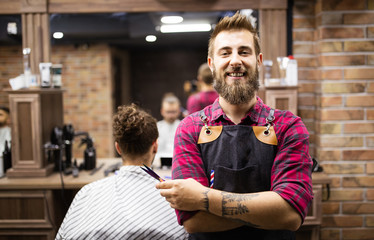 Portrait of happy young barber with client at barbershop and smiling.