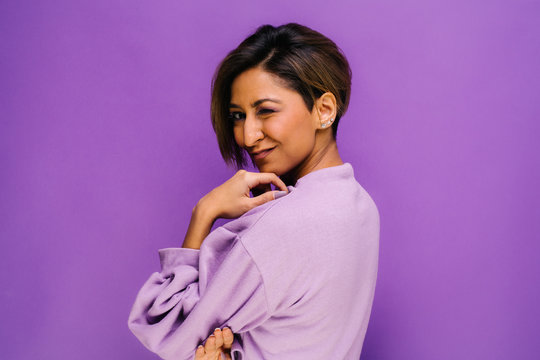 Portrait of young woman with her back to camera and short hair in the studio, with a purple background