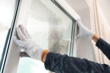 Fototapeta Worker installing plastic window indoors, closeup view obraz