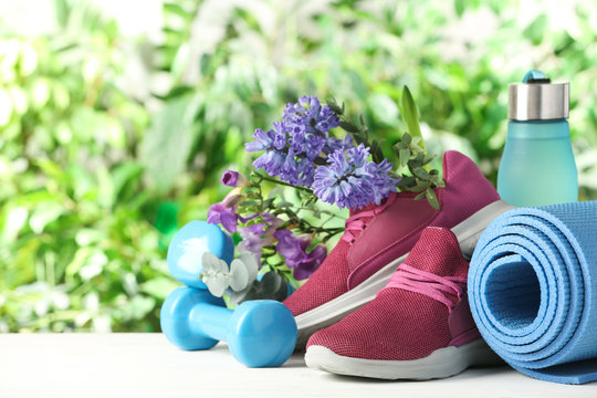 Composition with spring flowers and sports items on blurred green background