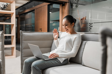 happy asian businesswoman waving hand while sitting on couch and having video chat on laptop