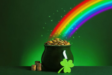 Pot with gold coins and clover on table against dark background. St. Patrick's Day