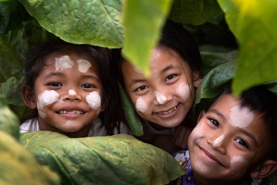 Three children, a happy gym in Burma, smiling, local children in tobacco fields.