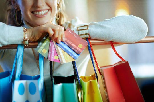 Closeup on woman near shopping bags with fan of credit cards